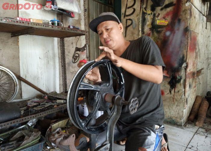 Rudi Andali, pemilik bengkel Rudi Stel Velg Motor sedang memperbaiki pelek yang peang.