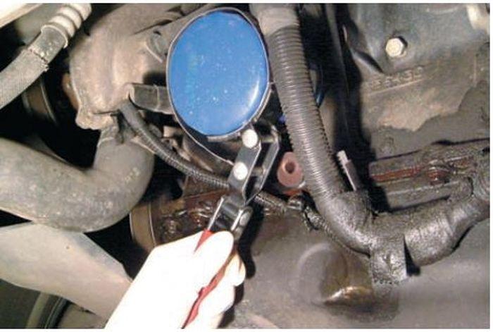 Ilustrasi melepas filter oli mesin mobil dengan menggunakan filter wrench