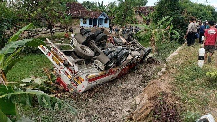 Warga melihat truk tangki yang terjun ke parit hingga terbalik di Jalan Raya Surabaya-Madiun, Jumat (28/5/2021).