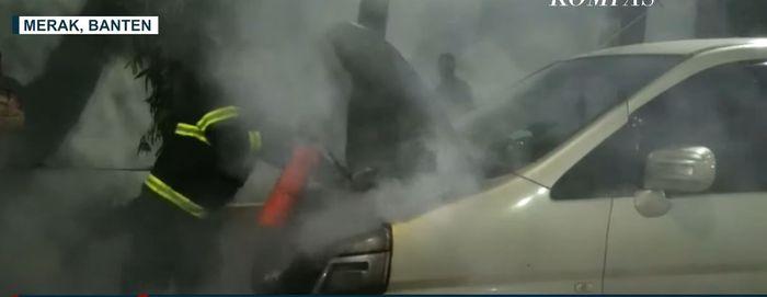Proses pemadaman api yang membakar mesin Nissan Serena C24 di Pelabuhan Merak, Cilegon, Banten