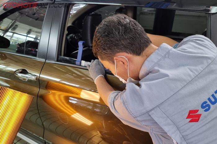 Teknisi body repair beres Suzuki SBT Pulogadung tengah melakukan PDR pada bodi Suzuki XL7