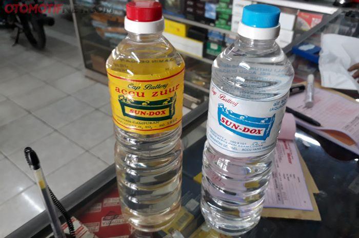 Accu zuur tutup botolnya berwarna merah (kiri) sedang air aki/air suling yang tutupnya warna biru