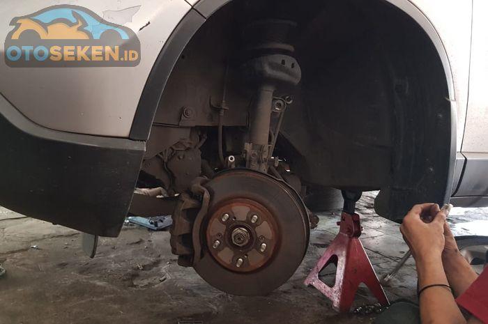 Ilustrasi sokbreker mobil bekas yang diperbaiki di bengkel