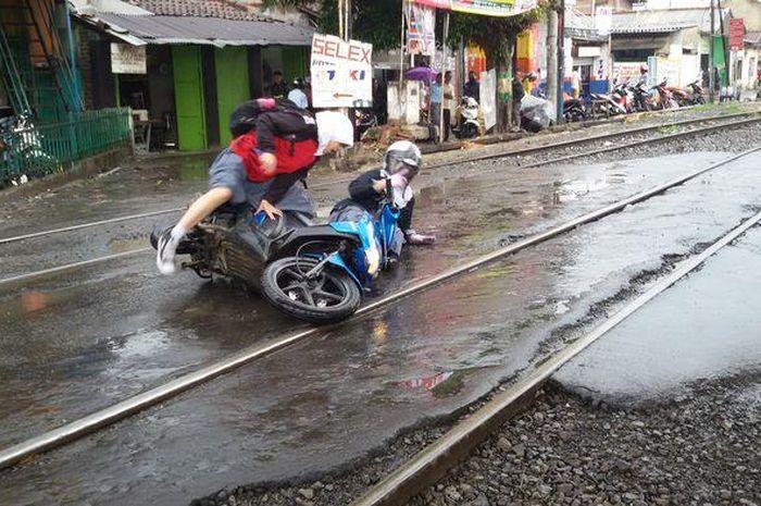 Dua orang pengendara motor terjatuh akibat rel kereta api yang licin. Ini Trik Aman Melintasi Rel Kereta Api, Pemotor Wajib Tahu