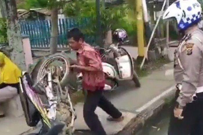 Seorang pria membanting motornya karena diberhentikan polisi tak memakai helm di Jalan Ahmad Yani, Rengat, Riau, Jumat (21/2/2020)
