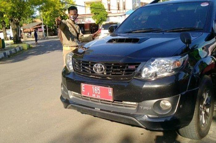 Kendaraan pelat merah berjenis Toyota Fortuner bernopol E 165 H saat menerobos petugas keamanan saat terjaring razia PSBB di Bunderan Kijang Indramayu, Selasa (12/5/2020).