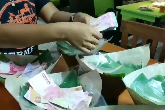 Nasi bungkus yang diselipi dengan beberapa uang berjumlah besar