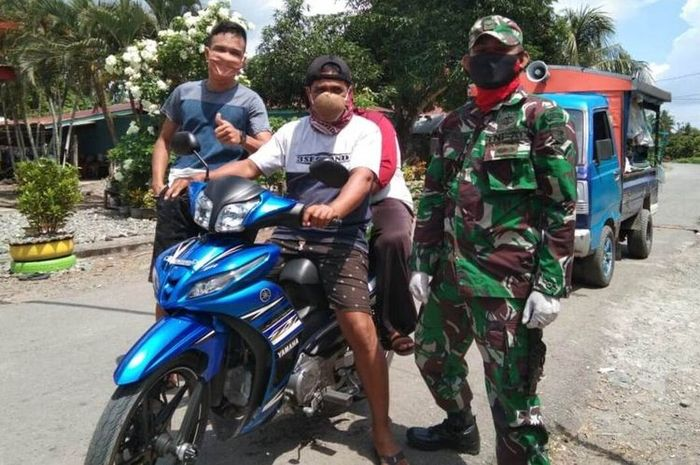 Pengendara roda dua yang melintas di Posko Covid-19 perbatasan antara Desa Bakti dengan Desa Lampuara, Kecamatan Ponrang Selatan, Kabupaten Luwu, Sulawesi Selatan, didapati Babinsa mengenakan masker dari batok tempurung kelapa, Kamis (21/05/2020)