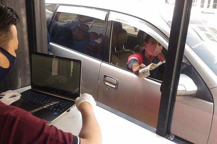 Salah seorang masyatakat tengah melakukan pelayanan tilang drive true yang baru dibuka hari ini, Rabu 10 Juni 2020. Urus Tilang di Bandar Lampung Kini Makin Mudah, Kejari Hadirkan Program TTD dan Drive Thru