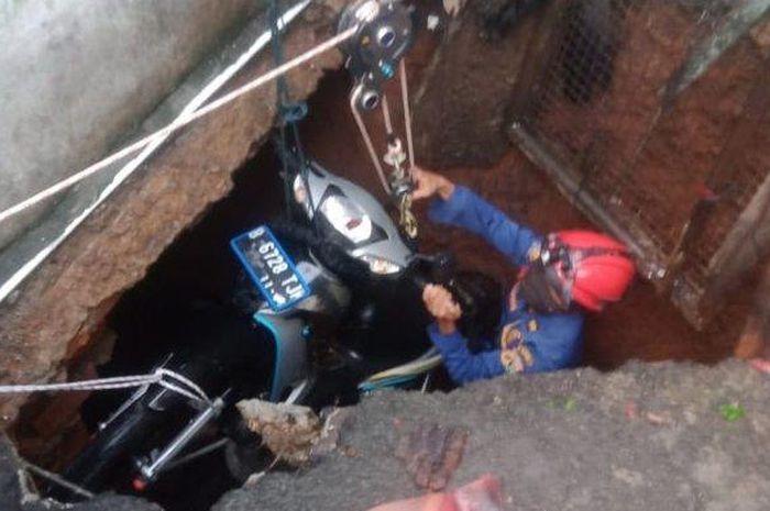 Proses pengangkatan motor yang terperosok ke dalam lubang septic tank di Gang Dahlia, Balekambang, Kramat Jati, Jakarta Timur, pada Selasa (21/7/2020) sore.