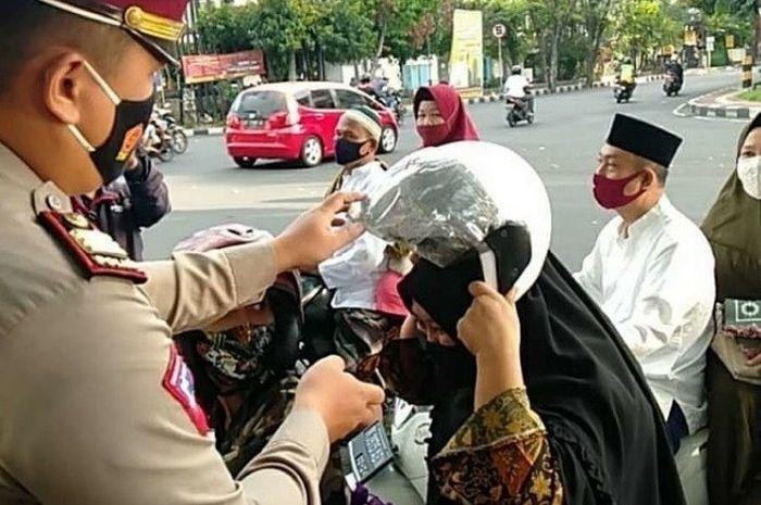 Personel Satlantas Polresta Denpasar tengah membagikan puluhan helm ke pengendara motor saat Hari Raya Idul Adha 1441 H, Jumat (31/07/2020).