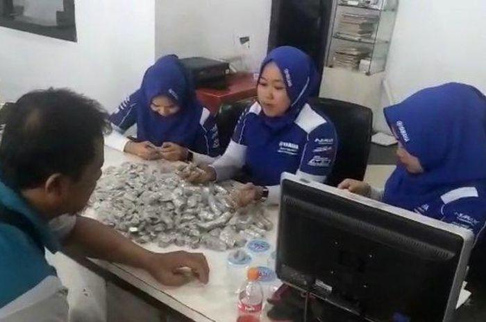 Tiga sales Suraco Jaya Abadi Motor Mamuju menghitung uang koin yang digunakan Solikhin membeli motor Nmax.