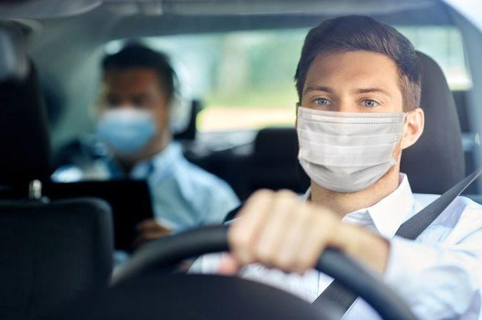Ilustrasi memakai masker di dalam mobil. Ahli ingatkan meski di dalam mobil yang tertutup, masker lebih baik tetap dikenakan.