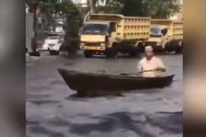 Seorang kakek mengayuh perahu di jalanan  banjir di jalan protokol Banjarmasin (Youtube Tribun Timur)