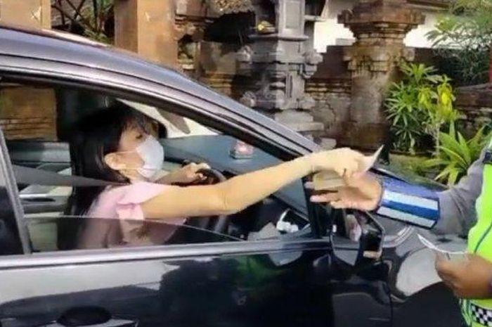 Anggota Satlantas Polresta Denpasar dari Unit Turjawali memberhentikan pelanggar lalu lintas di Jalan Imam Bonjol, Denpasar, Bali pada Rabu 17 Februari 2021