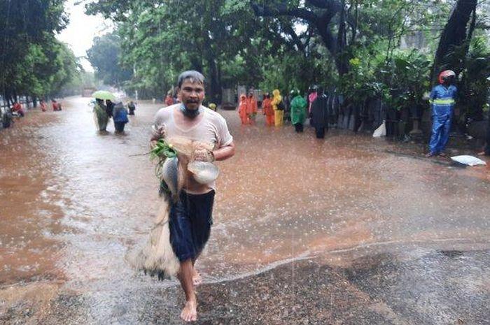 Warga menangkap ikan saat banjir di Jalan TB Simatupang, Jakarta Selatan, Sabtu (20/2/2021).
