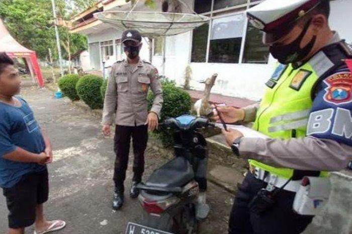 Petugas polisi saat menilang Bagas di posko penyekatan jembatan timbang, Klakah, Lumajang, Jumat (7/5/2021).