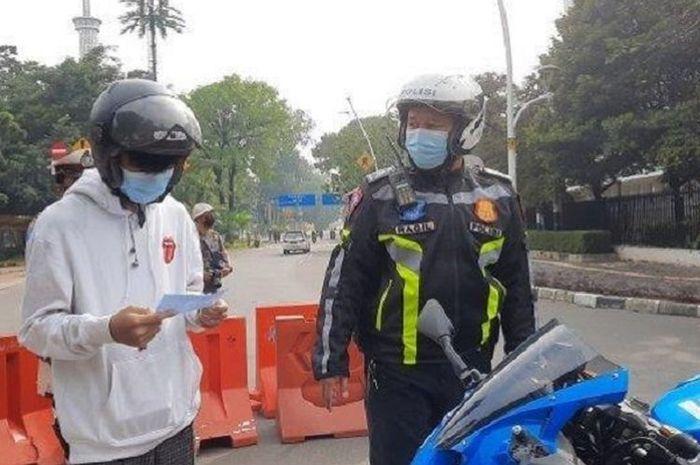 Remaja 16 tahun Rafly (kiri) ditilang polisi dalam razia Sunmori di Monas, Gambir, Jakarta Pusat, Minggu (7/3/2021). (WARTA KOTA Live.com/Desy Selviany)