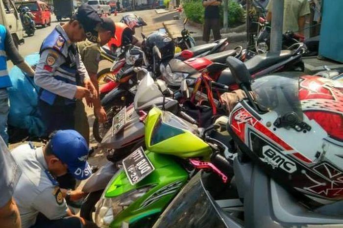 Kendaraan pengunjung di Pasar Pagi dicabut pentil petugas Suku Dinas Perhubungan dan Transportasi (Sudinhubtrans) Kecamatan Tambora, (22/11/2018)