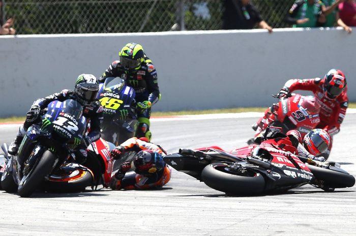 Andrea Dovizioso (kanan) jatuh setelah diseruduk Jorge Lorenzo (kiri, jatuh) di lap kedua MotoGP Catalunya